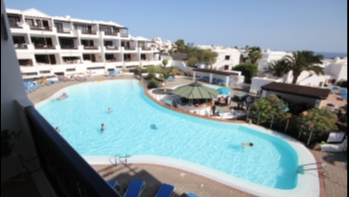 Top floor apartment with stunning pool & sea views in Costa Teguise